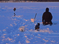 image of ice fishing holes augered in a line