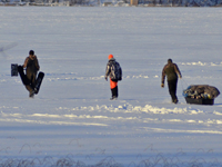 Image of ice fishermen walking on lake