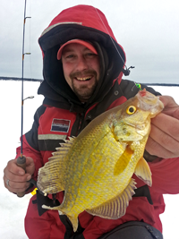 image of Zach Dagel holding Crappie on ice fishing trip