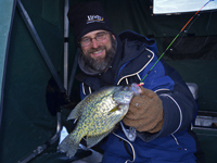 image of Jeff Samsel holding Crappie in ice fishing shelter