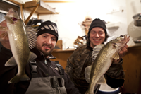 image of Nik Dimich and Justin Harms holding Walleyes inside of fishing shelter