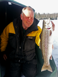 image of ice fisherman holding Rainbow Trout on Ice