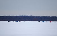 image of ice fishermen on round lake