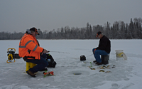 image of ice fishermen with perch on the ice